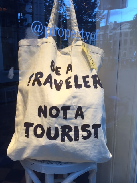 Traveler not Tourist - spotted in a window in Amsterdam image: Renee Middlemost
